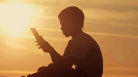 Menino com a tabuleta no por do sol que senta-se na montanha Imagem de Stock
