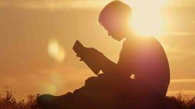 Menino com a tabuleta no por do sol que senta-se na montanha Fotografia de Stock