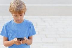 Menino com telefone celular na rua Criança que olha a tela, jogando jogos, usando apps Fundo da cidade escola Imagens de Stock Royalty Free