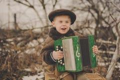 Menino com um acordeão Fotografia de Stock