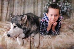 Menino com um cão na cama Imagens de Stock Royalty Free