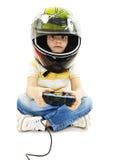 Menino com um capacete, usando o controlador do jogo de vídeo Imagem de Stock