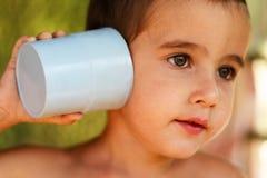 Menino com um dispositivo de comunicação do brinquedo Fotografia de Stock