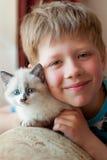 Menino com um gatinho na sala Fotografia de Stock Royalty Free