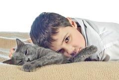 Menino com um gato em um fundo branco Fotografia de Stock Royalty Free