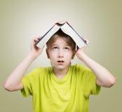 Menino com um livro em sua cabeça Fotos de Stock Royalty Free