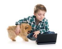 Menino com um portátil e um cachorrinho Imagens de Stock Royalty Free