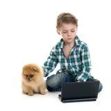 Menino com um portátil e um cachorrinho fotografia de stock