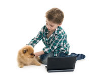 Menino com um portátil e um cachorrinho Fotografia de Stock Royalty Free