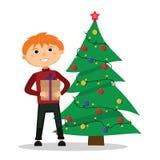 Menino com um presente nas mãos perto da árvore de Natal Imagens de Stock
