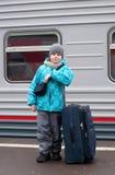 menino com um saco do curso perto de um trem Imagens de Stock Royalty Free