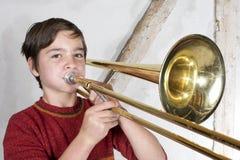 Menino com um trombone Fotos de Stock Royalty Free