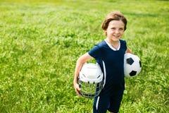 Menino com uma bola de futebol e um capacete do hóquei, na perspectiva da grama Foto de Stock