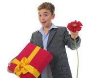Menino com uma caixa de presente e uma flor Imagem de Stock