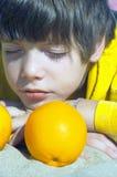 Menino com uma laranja imagens de stock
