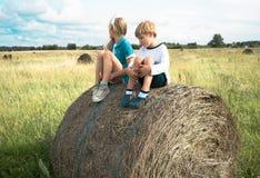 Menino com uma menina que senta no monte de feno o fundo de prados do verão Fotografia de Stock Royalty Free