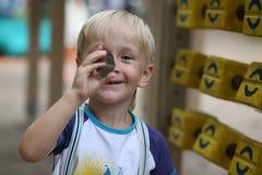 Menino com uma pedra pequena em sua mão Imagem de Stock