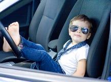 Menino com vidros e laço que senta-se no carro Fotografia de Stock Royalty Free