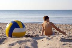 Menino com voleibol na praia. fotografia de stock
