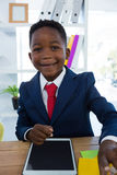 Menino como o executivo empresarial que sorri ao sentar-se no escritório foto de stock royalty free