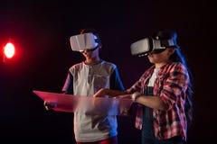 Menino concentrado e uma menina que joga jogos de VR imagem de stock royalty free