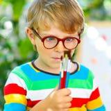 Menino confuso da criança com os vidros que guardam aquarelas e escovas A criança e o estudante felizes são de volta à escola foto de stock