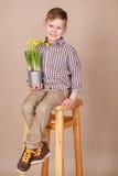 Menino considerável bonito em um assoalho de madeira com as flores na cesta que veste a calças e botas à moda da camisa foto de stock royalty free