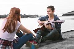Menino considerável com a guitarra que sente alegre ao sentar-se perto do rio com seu amigo fotos de stock royalty free