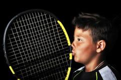 Menino considerável com a raquete de beijo do equipamento do tênis Imagens de Stock Royalty Free