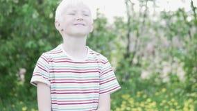 Menino consider?vel do albino que anda no parque em um dia de ver?o video estoque