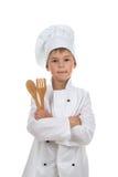 Menino considerável na cutelaria de madeira guardando uniforme do cozinheiro chefe, isolada no fundo branco imagens de stock