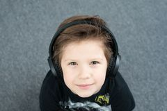Menino considerável nos fones de ouvido fotografia de stock