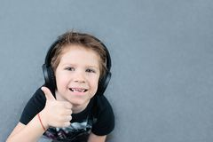 Menino considerável nos fones de ouvido que escuta a música foto de stock