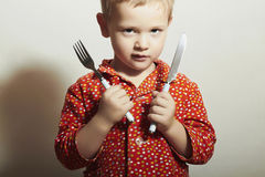 Menino considerável pequeno com forquilha e Knife.Hungry imagem de stock royalty free