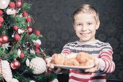 Menino considerável que dá às cookies de Santa Claus no Natal Foto de Stock Royalty Free