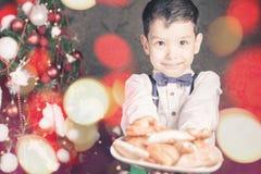 Menino considerável que dá às cookies de Santa Claus no Natal Fotografia de Stock