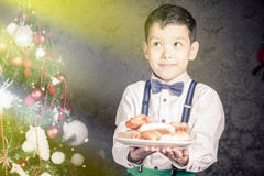 Menino considerável que dá às cookies de Santa Claus no Natal Fotos de Stock Royalty Free