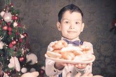 Menino considerável que dá às cookies de Santa Claus no Natal Fotos de Stock