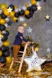 Menino considerável que levanta em decorações do partido com a estrela dourada grande enorme Fundo cinzento estrelas de prata e b imagens de stock royalty free