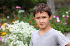 Menino contra a flor do verão Fotografia de Stock Royalty Free