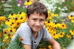 Menino contra a flor do verão Foto de Stock