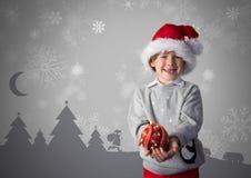Menino contra o fundo cinzento com chapéu de Santa e roupa do Natal e ilustrações do Natal ilustração do vetor