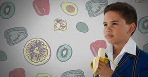 Menino contra o fundo cinzento com ilustrações da banana e das frutas e legumes fotos de stock royalty free