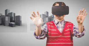 Menino contra o fundo cinzento com os auriculares da realidade virtual e as construções 3D Fotografia de Stock
