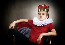 Menino coroado que senta-se em uma poltrona fotografia de stock