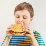 Menino cortado novo em uma camisa listrada que come um Hamburger saboroso no fundo branco imagens de stock