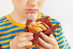 Menino cortado pequeno com um bolo de maçã apetitoso no fim branco do fundo acima fotos de stock
