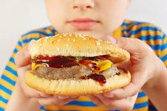 Menino cortado pequeno com um Hamburger saboroso no fim branco do fundo acima imagem de stock