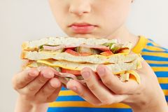Menino cortado pequeno com um sanduíche dobro saboroso no fim branco do fundo acima fotografia de stock royalty free