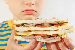 Menino cortado pequeno com um sanduíche saboroso no fim branco do fundo acima fotografia de stock royalty free